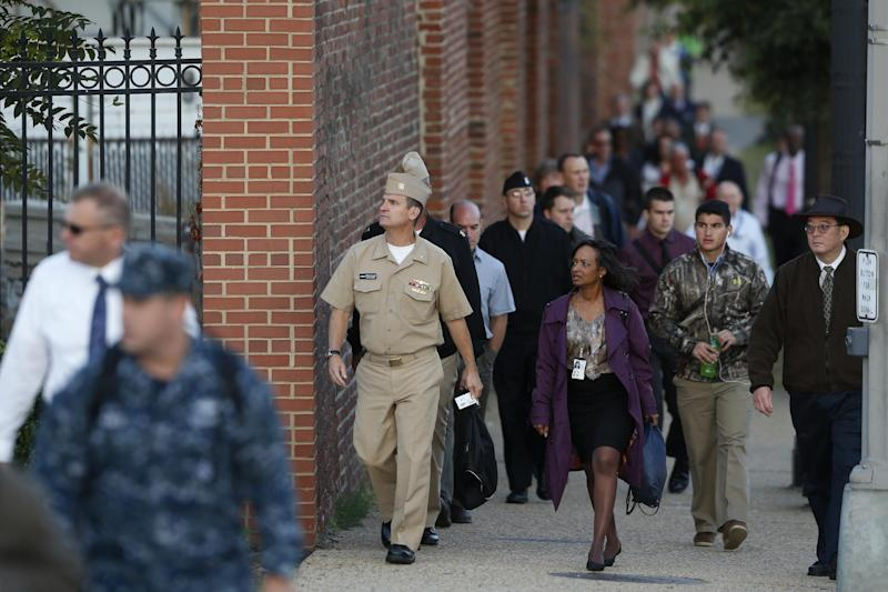 Military personnel and workers walk along the perimeter of the Washington Navy Yard Thursday, Sept. 19, 2013. The Washington Navy Yard reopened for normal operations Thursday with returning employees saying they still felt unsettled about the shooting there earlier this week in which a gunman killed 12 people. (AP Photo/Charles Dharapak)