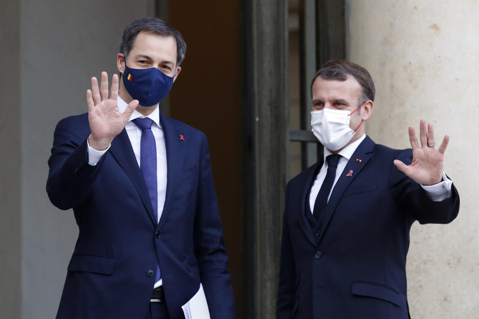 French President Emmanuel Macron, right, and Belgium's Prime Minister Alexander De Croo, wave to journalists prior to a meeting, at the Elysee Palace, in Paris, France, Tuesday, Dec. 1, 2020. (AP Photo/Thibault Camus)