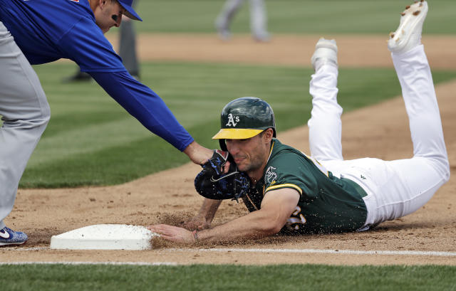 Oakland Athletics' Matt Olson, right, dives safely back to first base on a pickoff attempt as Chicago Cubs first baseman Anthony Rizzo comes in with the tag during the first inning of a spring training baseball game Wednesday, March 13, 2019, in Mesa, Ariz. (AP Photo/Elaine Thompson)