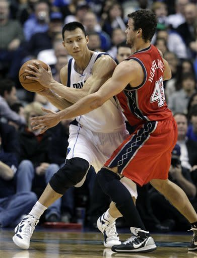 Dallas Mavericks' Yi Jianlian (9), of China, attempts to get past New Jersey Nets' Kris Humphries (43) in the first half of an NBA basketball game, Tuesday, Feb. 28, 2012, in Dallas. (AP Photo/Tony Gutierrez)