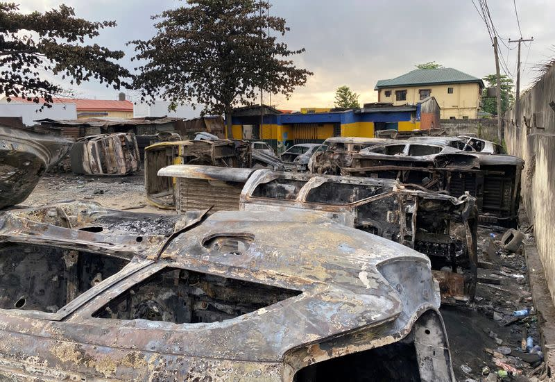 Burnt vehicles are pictured at a damaged police station in Lagos