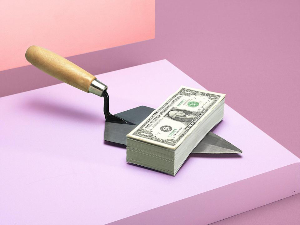 money on a spade with a pink background