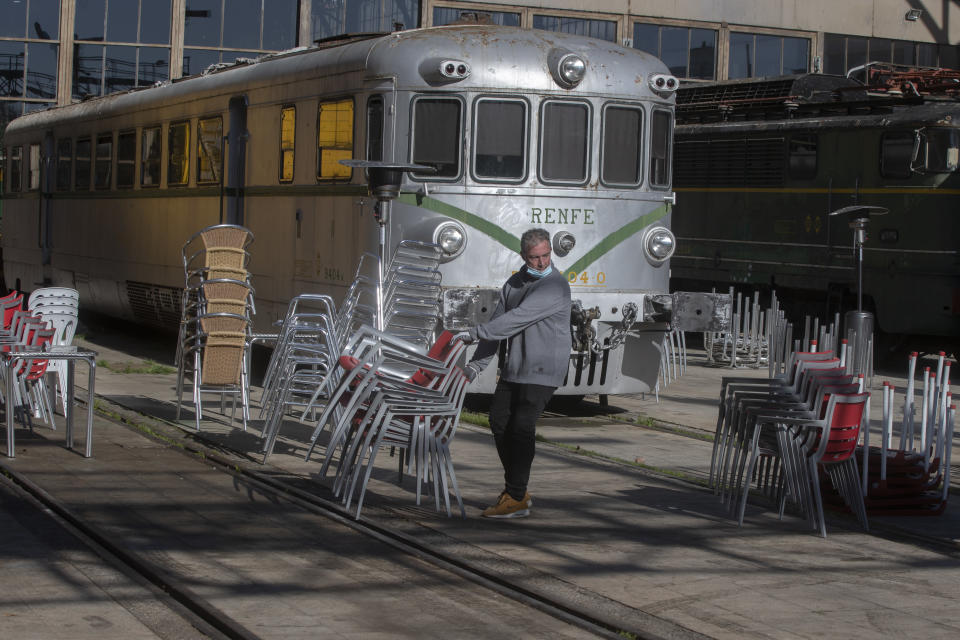 A bar worker sets out tables and chairs in a terrace bar outside an old train station which is currently a railway museum, in Madrid, Spain, Sunday, Feb. 14, 2021. Several central Spanish regions including Madrid have announced some easing of curfews and restrictions on bar and restaurants despite warnings to keep a high alert despite a slowing curve of the Coronavirus contagion. (AP Photo/Paul White)