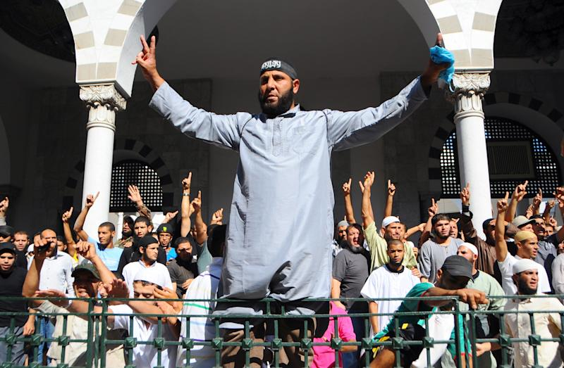 Tunisian activists stage a protest outside the El Fateh mosque in Tunis, surrounded by police, in support of a hardline Muslim, known as Abu Yadh, Monday, Sept. 17, 2012. The Salafi retreated inside with dozens of supporters after a fiery denunciation of the Tunisian government. Police surrounded the mosque but did not enter. (AP Photo/Hassene Dridi)