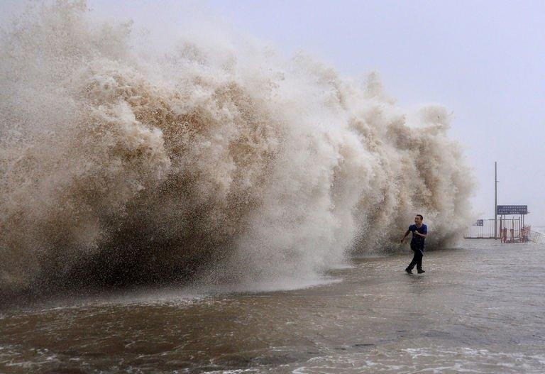 A man running away from a huge wave in Shantou, southern China September 22, 2013