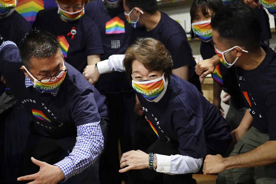 Tokyo 2020 Organizing Committee President Seiko Hashimoto, center, wearing a rainbow-colored mask poses for a photo with representatives and staff at Pride House Tokyo Legacy during her visit, in Tokyo Tuesday, April 27, 2021. Japan marked LGBTQ week with pledge to push for equality law before the Olympics. (AP Photo/Eugene Hoshiko, Pool)