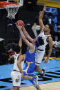 UCLA guard Jaime Jaquez Jr., center, drives to the basket between Gonzaga guard Jalen Suggs (1) and forward Anton Watson, right, during the first half of a men's Final Four NCAA college basketball tournament semifinal game, Saturday, April 3, 2021, at Lucas Oil Stadium in Indianapolis. (AP Photo/Darron Cummings)