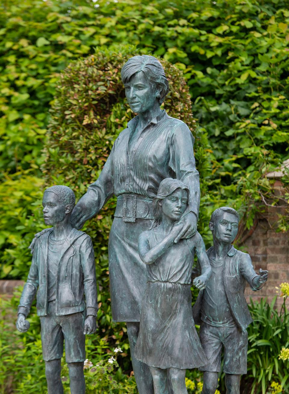 The statue of Diana, Princess of Wales, by artist Ian Rank-Broadley, unveiled by Britain's Prince William, Duke of Cambridge and Britain's Prince Harry, Duke of Sussex, is pictured at The Sunken Garden in Kensington Palace, London on July 1, 2021, which would have been her 60th birthday. - The bronze statue depicts the princess surrounded by three children to represent the