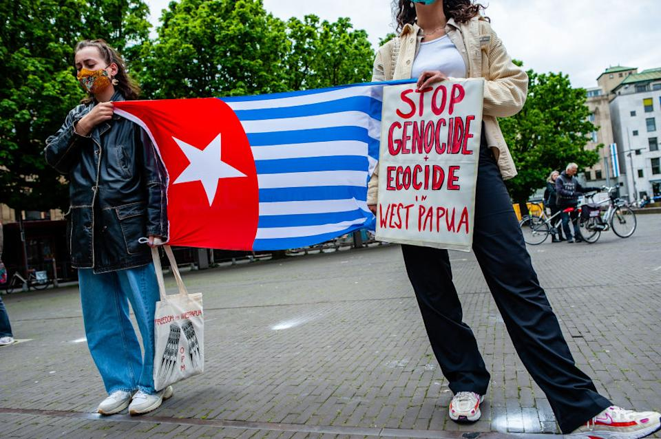 Two women are seen holding a Papuan flag and a placard in solidarity with West Papua during a demonstration at the Hague this month