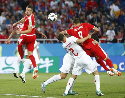 Serbia's Sergej Milinkovic-Savic, left, heads the ball as Serbia's Aleksandar Mitrovic and Switzerland's Stephan Lichtsteiner challenge during the group E match between Switzerland and Serbia at the 2018 soccer World Cup in the Kaliningrad Stadium in Kaliningrad, Russia, Friday, June 22, 2018. (AP Photo/Matthias Schrader)