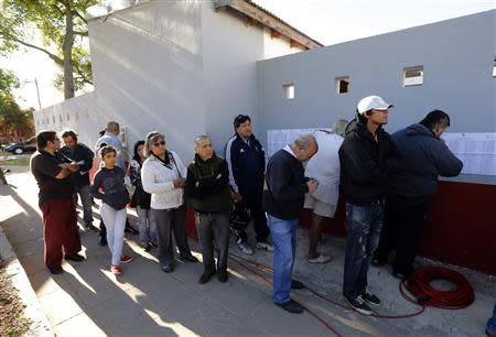 Citizens line up to vote in nationwide congressional elections outside a public school in Buenos Aires