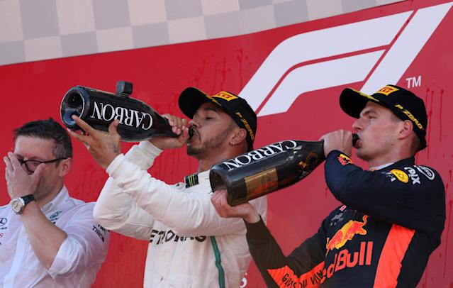 Formula One F1 - Spanish Grand Prix - Circuit de Barcelona-Catalunya, Barcelona, Spain - May 13, 2018 Mercedes' Lewis Hamilton and Red Bull's Max Verstappen drink champagne as they celebrate on the podium after finishing first and third respectively REUTERS/Albert Gea