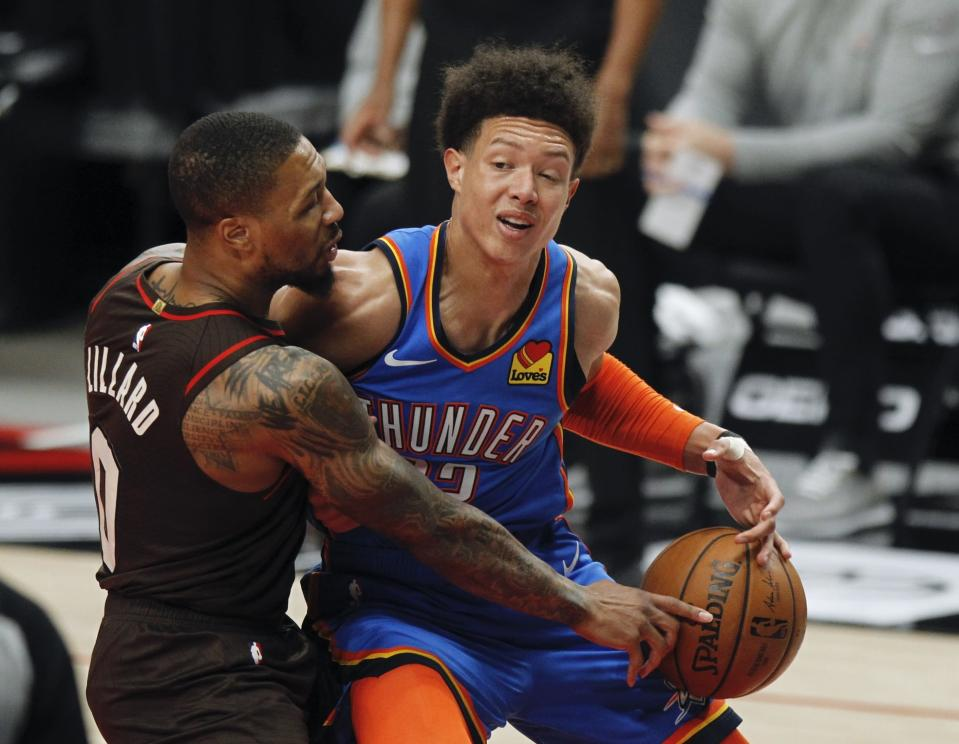 Oklahoma City Thunder center Isaiah Roby, right, has the ball knocked away by Portland Trail Blazers guard Damian Lillard, left, during the first half of an NBA basketball game in Portland, Ore., Saturday, April 3, 2021. (AP Photo/Steve Dipaola)
