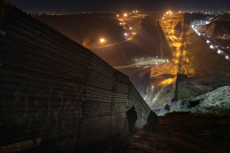 Migrants look for a place to jump the border fence to get into the U.S. side from Tijuana, Mexico