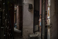 A young girl stands at the entrance of her house next to the house of a 9-year-old girl from the lowest rung of India's caste system who according to her parents and protesters, was raped and killed earlier this week, in New Delhi, India, Thursday, Aug. 5, 2021. (AP Photo/Altaf Qadri)