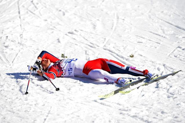 SOCHI, RUSSIA - FEBRUARY 13: Marit Bjoergen of Norway collapses at the finish line in the Women's 10 km Classic during day six of the Sochi 2014 Winter Olympics at Laura Cross-country Ski & Biathlon Center on February 13, 2014 in Sochi, Russia. (Photo by Harry How/Getty Images)