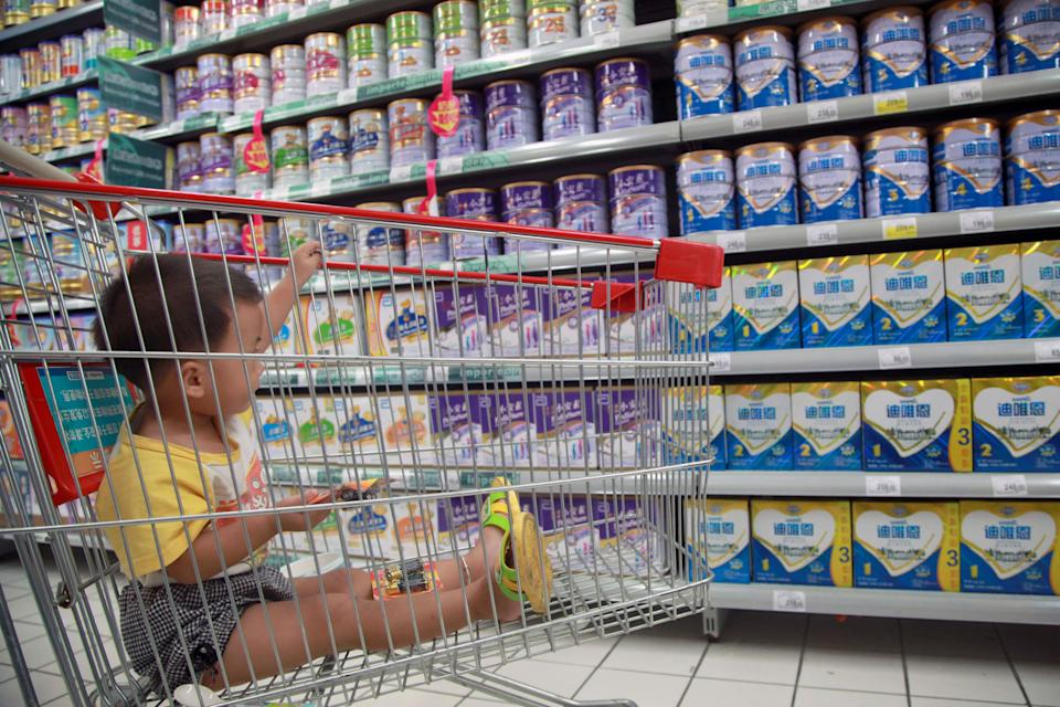 A child gazes on at tins of formula inside a Chinese supermarket. Source: Getty