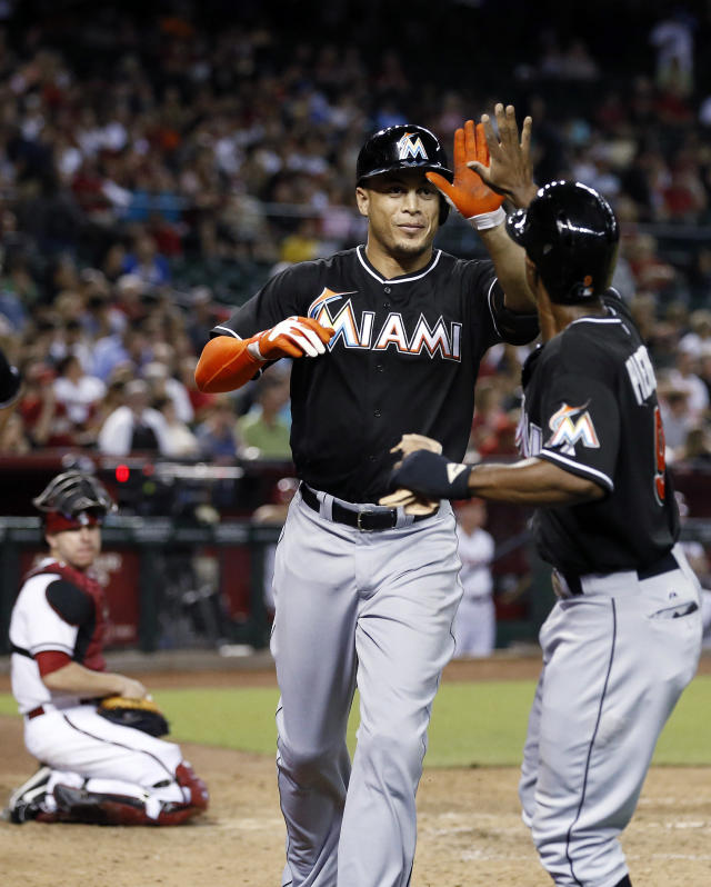 Miami Marlins' Giancarlo Stanton gets a high-five from teammate Juan Pierre, right, after Stanton hits a two-run home run, as Arizona Diamondbacks' Miguel Montero, left, looks on during the sixth inning of a baseball game on Monday, June 17, 2013, in Phoenix. (AP Photo/Ross D. Franklin)