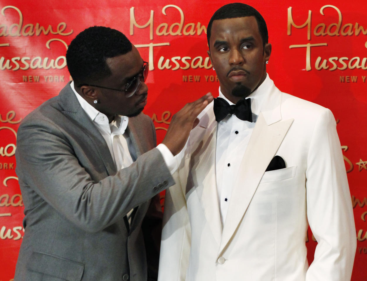 """Sean """"Diddy"""" Combs touches his wax figure at Madame Tussauds in New York, December 15, 2009. REUTERS/Shannon Stapleton"""
