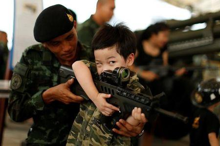 A Thai army soldier gives a weapon to a boy to pose for a picture during Children's Day celebration at a military facility in Bangkok, Thailand January 14, 2017. REUTERS/Jorge Silva