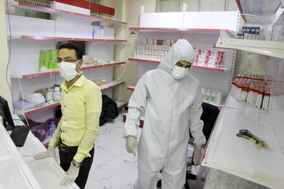In this May 12, 2020 photo, Yemeni medical workers wearing masks and protective gear stand at the entrance of a hospital in Aden, Yemen. People have been dying by the dozens each day in southern Yemen's main city, Aden, many of them with breathing difficulties, say city officials. Blinded with little capacity to test, health workers fear the coronavirus is running out of control, feeding off a civil war that has completely broken down the country. (AP Photo/Wail al-Qubaty)