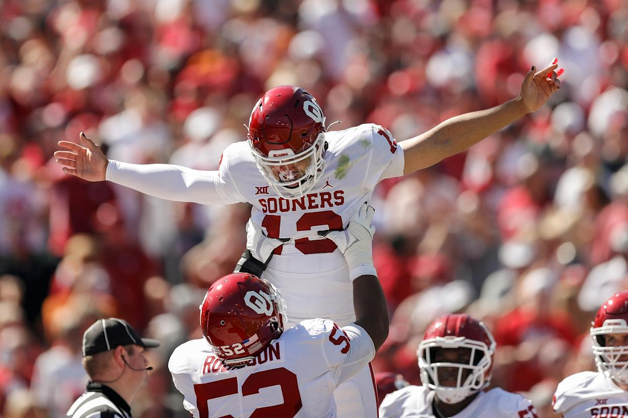 DALLAS, TEXAS - OCTOBER 09: Tyrese Robinson #52 of the Oklahoma Sooners celebrates with Caleb Williams #13 of the Oklahoma Sooners after a touchdown in the first half against the Texas Longhorns during the 2021 AT&T Red River Showdown at Cotton Bowl on October 09, 2021 in Dallas, Texas. (Photo by Tim Warner/Getty Images)