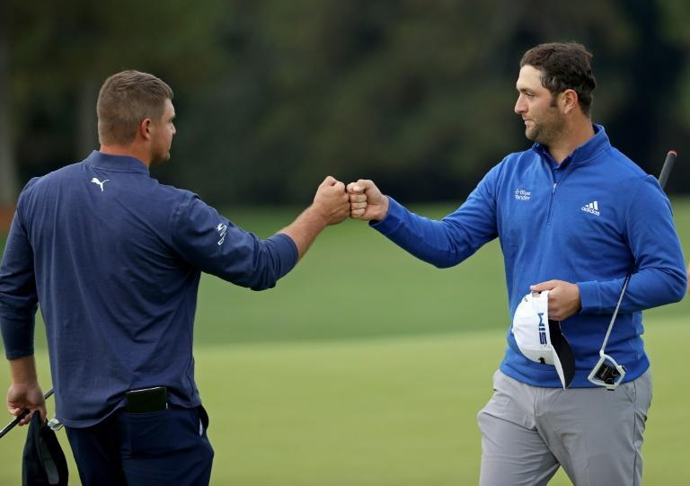 US Open champion Bryson DeChambeau, left, bumps fists with world number two Jon Rahm of Spain on Saturday after they finished their second rounds at the Masters