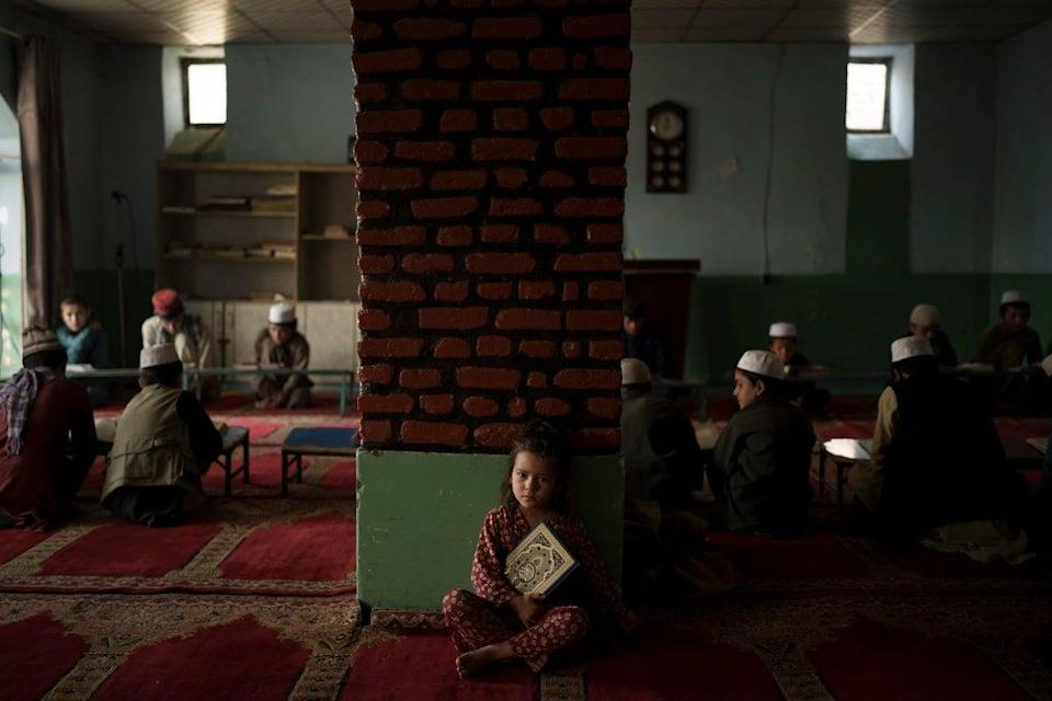 The niece of a teacher sits alone in a classroom as boys attend a class to memorise the Quran, Islam's holy book, at a madrasa in Kabul (AP)