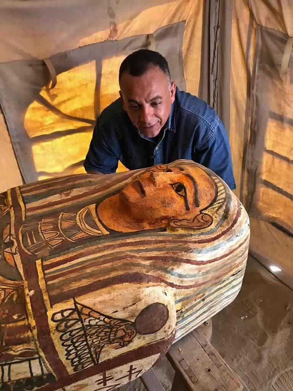 This Sept. 2020 photo provided by the Ministry of Tourism and Antiquities shows Mostafa Waziri, secretary general of the Supreme Council of Antiquities, posing with one of more than two dozen ancient coffins unearthed near the famed Step Pyramid of Djoser in Saqqara, south of Cairo, Egypt. (Ministry of Tourism and Antiquities via AP)