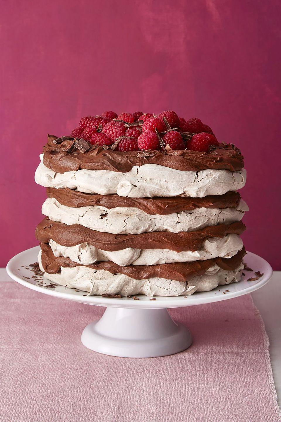 """<p>The fresh raspberries on top balance out the decadent layers of this chocolate meringue cake with chocolate mousse filling. </p><p><a href=""""https://www.womansday.com/food-recipes/food-drinks/a19124220/chocolate-meringue-layer-cake-recipe/"""" rel=""""nofollow noopener"""" target=""""_blank"""" data-ylk=""""slk:Get the recipe for Chocolate Meringue Layer Cake."""" class=""""link rapid-noclick-resp""""><em>Get the recipe for Chocolate Meringue Layer Cake.</em></a><br></p>"""