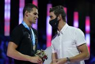 Michael Andrew talks to Michael Phelps at the medal ceremony for the men's 200 individual medley during wave 2 of the U.S. Olympic Swim Trials on Friday, June 18, 2021, in Omaha, Neb. (AP Photo/Charlie Neibergall)