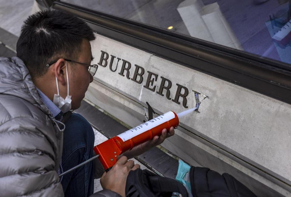A man repairs a damaged logo in front of a Burberry store in Shanghai. Burberry was the first luxury brand that suffered Chinese backlash over a controversy about sourcing cotton from Xinjiang. Photo: EPA-EFE