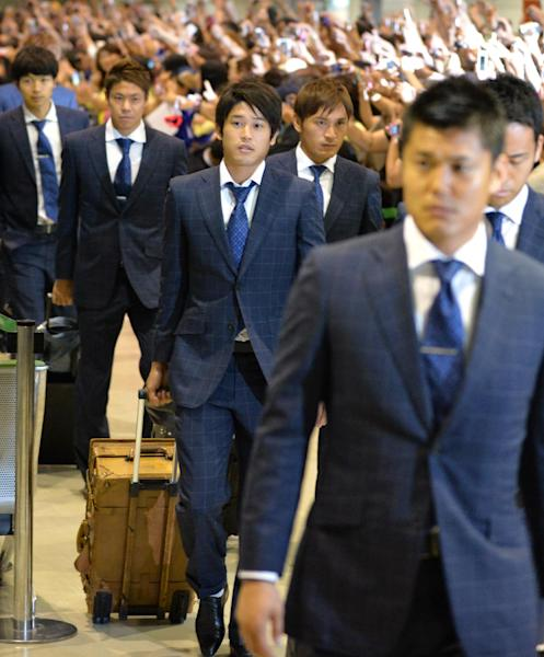 Japan's Atsuto Uchida (C) and his teammates return home after a winless campaign in Brazil, at Narita Airport near Tokyo, on June 27, 2014 (AFP Photo/Kazuhiro Nogi)