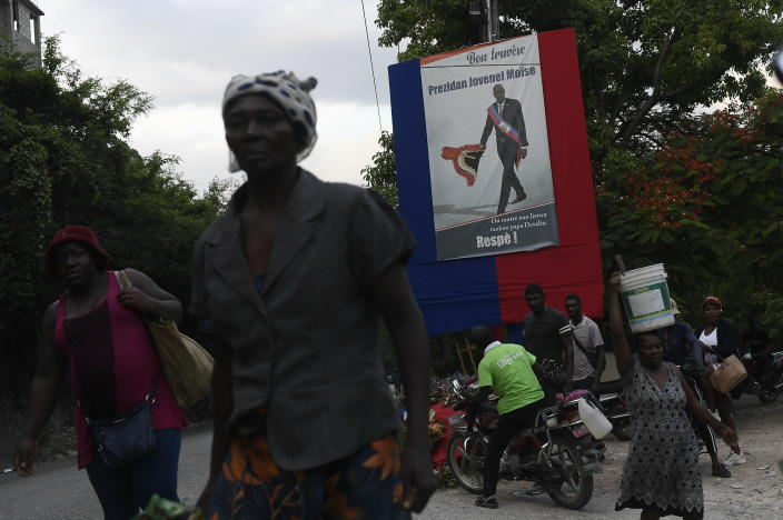 People walk near a poster featuring President Jovenel Moise in Port-au-Prince, Haiti, Saturday, July 17, 2021, ten days after Moise was assassinated in his home on July 7. (AP Photo/Matias Delacroix)