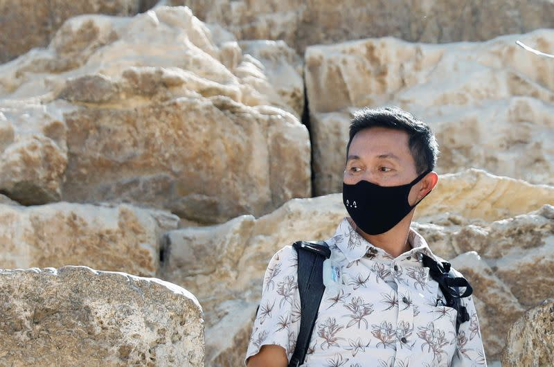 A tourist wears protective mask as a means of prevention against the coronavirus (COVID-19) at the Great Pyramids of Giza, on the outskirts of Cairo