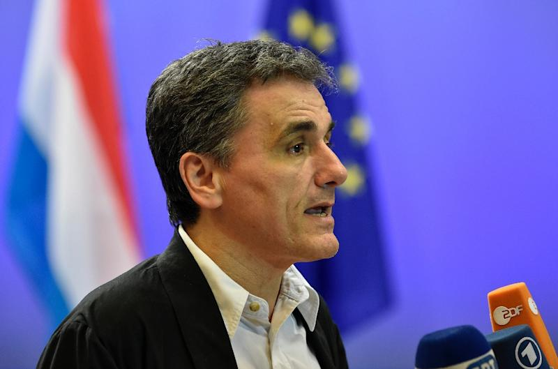 Greek Finance Minister Euclid Tsakalotos answers journalists after a meeting of the Eurogroup on Greece at the European Union headquarters in Brussels on August 14, 2015 (AFP Photo/John Thys)
