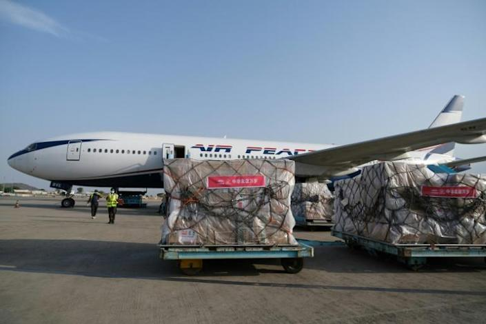 Airport employees at the international airport in Abuja, Nigeria unload medical equipment on April 8, 2020 as a team of Chinese medics arrived to help fight the coronavirus pandemic (AFP Photo/Kola Sulaimon)