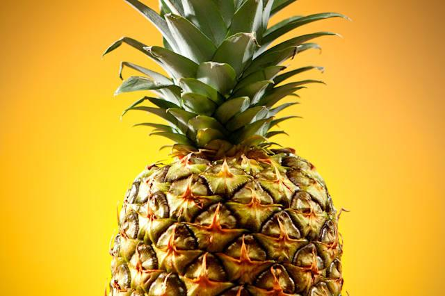 Pineapple with green leaves with bright yellow background.