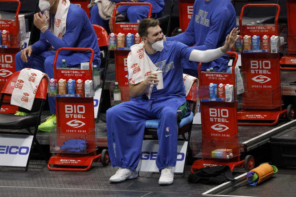 Dallas Mavericks guard Luka Doncic (77) waves to a fan from the bench as the Dallas Mavericks play the Minnesota Timberwolves during the first half of an NBA basketball game, Monday, Feb. 8, 2021, in Dallas. (AP Photo/Ron Jenkins)