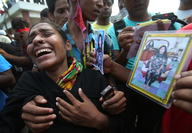 In this photograph taken on Wednesday, May 1, 2013, in Dhaka, Bangladesh, Farida, center, cries as she searches for her sister-in-law Fahima, seen in photographs. Just moments before Fahima was to be placed in one of the dozens of unmarked graves dug for victims of Bangladesh's building collapse, Farida was able to claim and leave with her sister-in-law's body. For Farida and countless other relatives of the garment workers who disappeared when Rana Plaza came crashing down, the past week has been one of tumbling expectations, as hope that their loved ones survived faded into the realization that they may have to return home without even a body to bury. (AP Photo/Wong Maye-E)