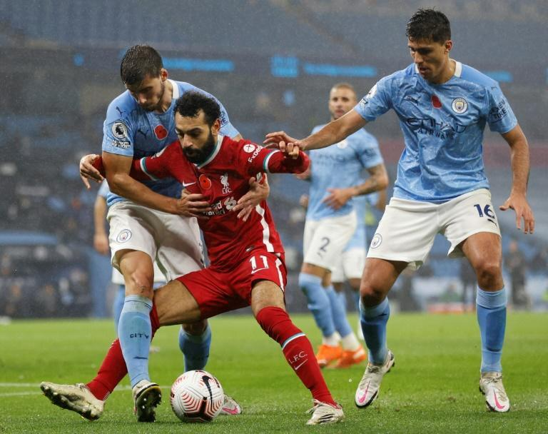 Liverpool forward Mohamed Salah (C) battles for possession against Manchester City in the English Premier League