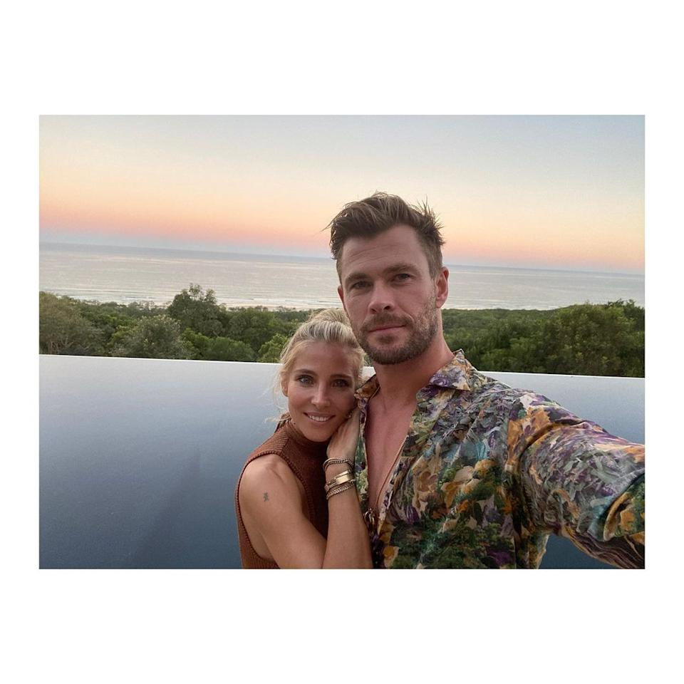 Elsa Pataky and Chris Hemsworth standing in front of a pool at sunset