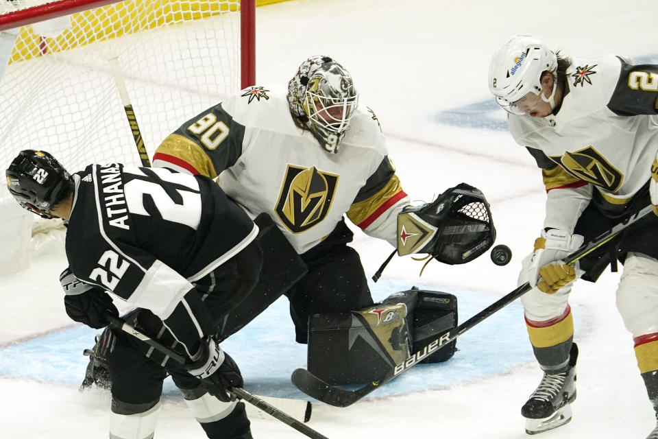 Los Angeles Kings left wing Andreas Athanasiou, left, tries to get a shot past Vegas Golden Knights goaltender Robin Lehner, center, as defenseman Zach Whitecloud defends during the first period of an NHL hockey game Monday, April 12, 2021, in Los Angeles. (AP Photo/Mark J. Terrill)