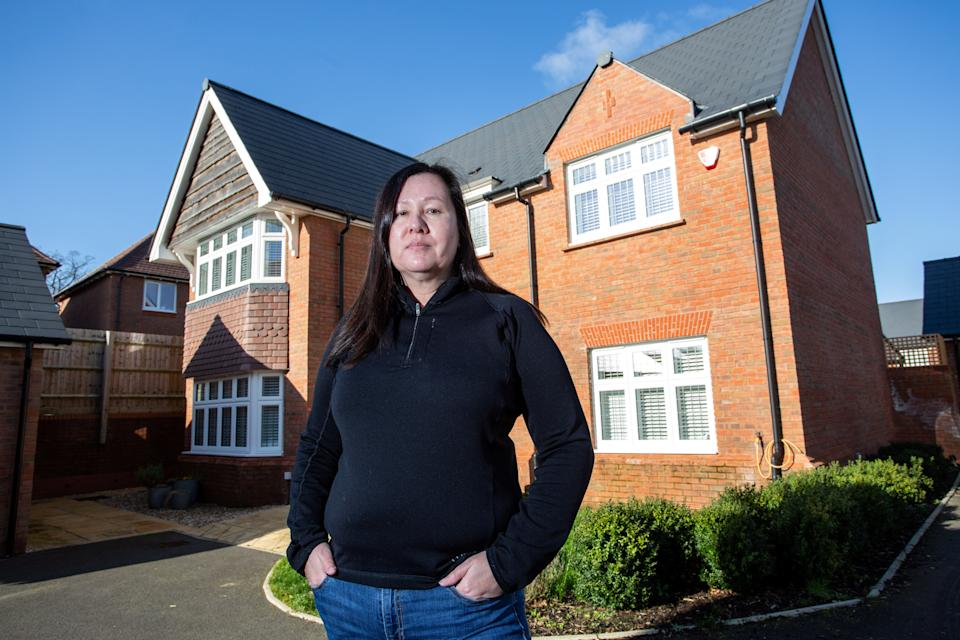 """Lucy Mitchell has had a catalogue of problems with a new-build property that cost her half a million pounds to buy. Swindon, Wiltshire. 06 February 2020. See SWNS story SWBRhome. A furious homeowner has condemned developers after she spent almost £500,000 on a new-build 'dream home' - only to find it is PLAGUED with drainage and electric faults. Airline pilot Lucy Mitchell paid £475,000 for the four-bedroom house in 2016 - but has had to spend another £25,000 fixing the electrics, drainage, and bathroom tiles. Lucy, 55, found issues all over the house, including no upstairs lights, broken thermostats throughout, and even wires on the boiler being """"deliberately"""" cut, she claims. The property is constantly damp, which Lucy claims, is down to a leaking tap at the front of the house, water leaks in her garage that run down the drive, and even cement blocking one of her toilets."""