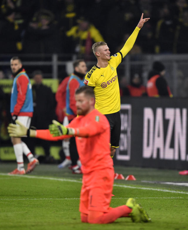 Dortmund's Erling Haaland, up, celebrates after scoring his side's 4th goal against Cologne's goalkeeper Timo Horn, down, during the German Bundesliga soccer match between Borussia Dortmund and 1. FC Cologne in Dortmund, Germany, Friday, Jan. 24, 2020. (AP Photo/Martin Meissner)