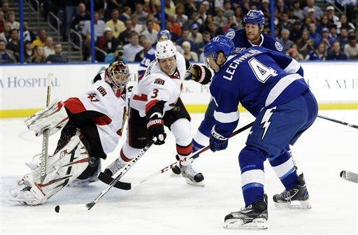 Tampa Bay Lightning center Vincent Lecavalier (4) flips the puck past Ottawa Senators defenseman Marc Methot (3) and goalie Craig Anderson (41) for a goal during the second period of an NHL hockey game, Tuesday, April 9, 2013, in Tampa, Fla. (AP Photo/Chris O'Meara)