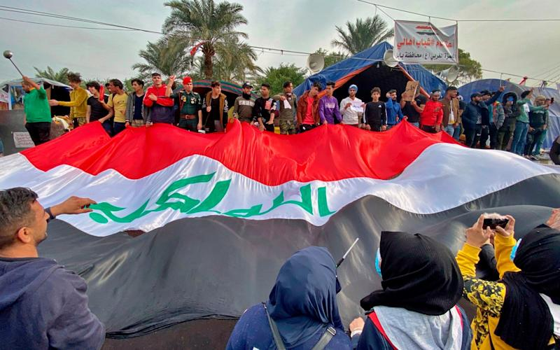 Anti-government protesters in Tahrir Square, Baghdad, hold a huge Iraqi flag after the lynching incident nearby was condemned by the wider protest movement - AP