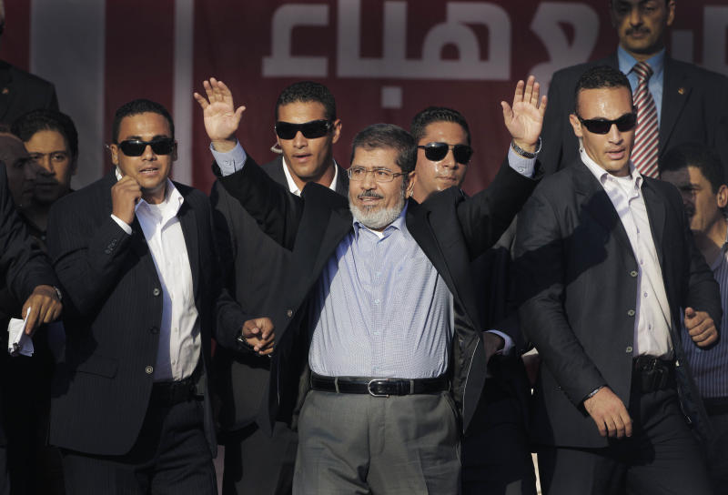FILE - In this Friday, June 29, 2012 file photo, Egypt's new President-elect Mohammed Morsi waves to supporters at Tahrir Square, the focal point of Egyptian uprising, in Cairo, Egypt. Standing before tens of thousands of adoring supporters in Tahrir Square, Morsi opened his jacket to show he is not wearing a bullet-proof vest. The message is clear: He has nothing to fear because he sees himself as the legitimate representative of Egypt's uprising. His speeches reveal a populist bent, making generous promises that many are skeptical he can keep. And though he began as an awkward and uninspiring speaker, he appears to be striving to reinvent his decidedly uncharismatic public persona. (AP Photo/Amr Nabil, File)