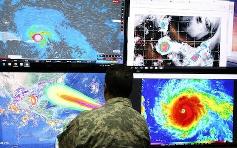 A member of the Emergency Operations Committee (COE) monitors the trajectory of Hurricane Irma in Santo Domingo, Dominican Republic - Credit: RICARDO ROJAS/Reuters