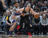 Denver Nuggets forward Mason Plumlee, right, scoops up a loose ball as Charlotte Hornets forward Miles Bridges defends during the first half of an NBA basketball game Wednesday, Jan. 15, 2020, in Denver. (AP Photo/David Zalubowski)